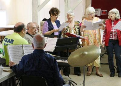 4 women rehearsing, men playing musical instruments rehearsing for GI Jukebox 2017
