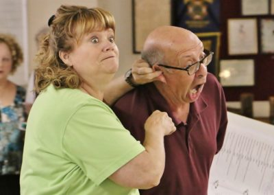 man and woman rehearsing - woman pulling man's ear