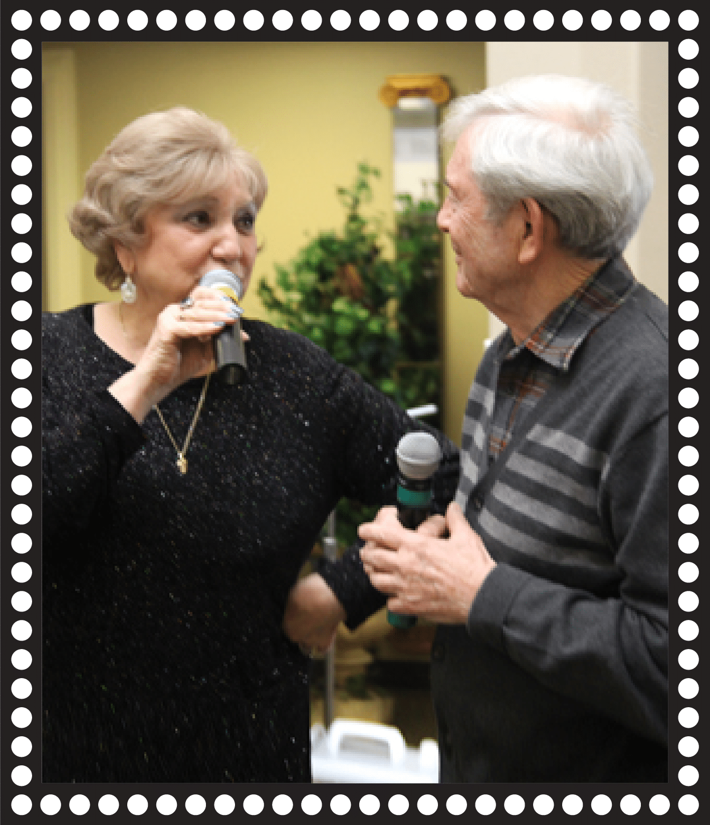 Man and woman singing together with microphone facing each other