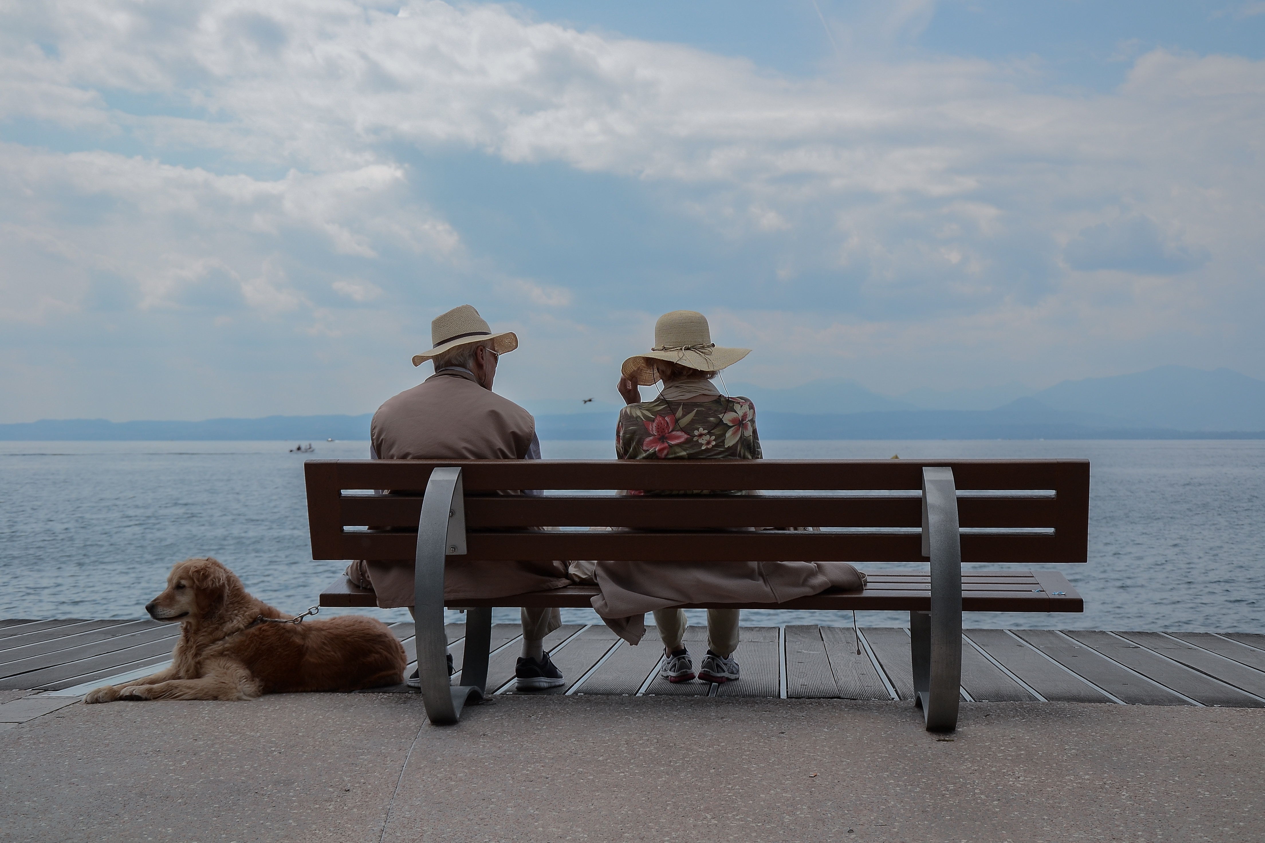 couple sitting on bench in front of lake discussing news