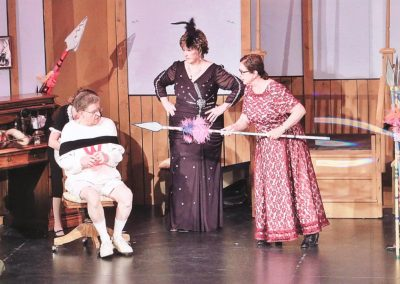 Woman holding spear at guy tied up in chair - Heart of the Hills Players Something's Afoot Performance 2018
